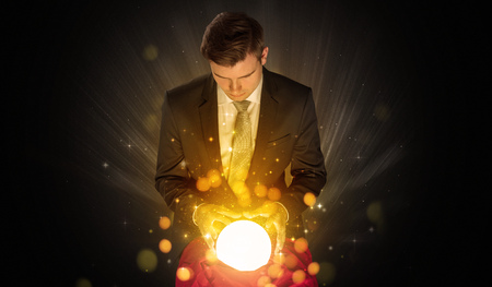 Businessman  sitting with sparkling magic ball Archivio Fotografico