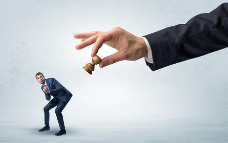 Grote hand met schaakstuk onderaan klein zwak zakenmanconcept Stockfoto