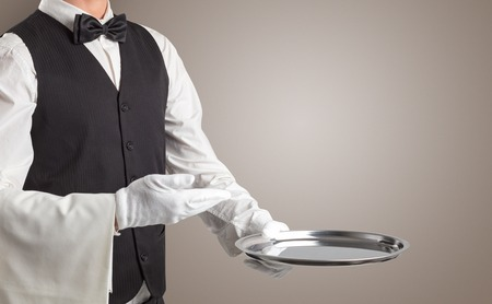 Waiter serving with white gloves and steel tray 免版税图像
