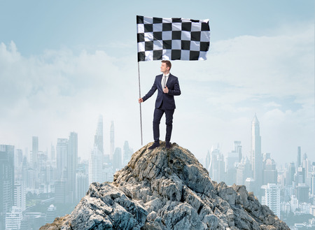 Businessman on the top of a city achieving his goal