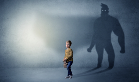 Cute kid with hero shadow behind Stockfoto - 114728302
