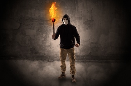 Wayfarer with burning torch in front of crumbly wall concept Stock Photo