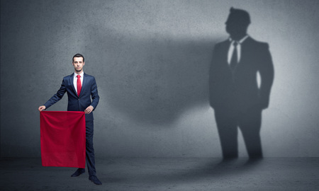 Businessman with toreador concept and his shadow on the background Standard-Bild