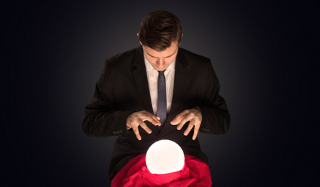 Handsome businessman with magic ball and dark empty background