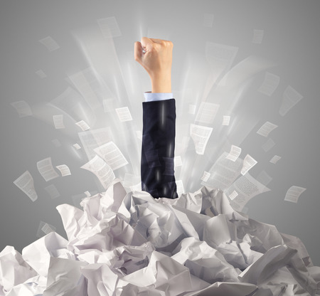 Hand coming out from paper pile Stock Photo - 115105740
