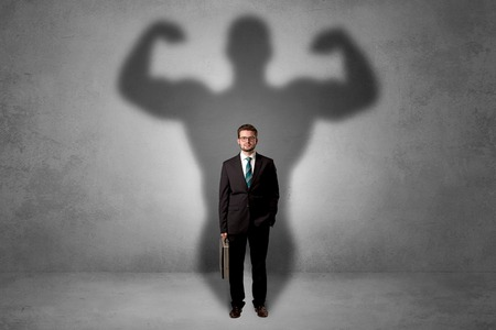 Businessman with muscular shade behind his back