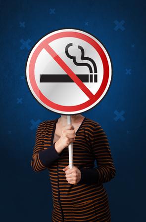 Woman holding no smoking sign