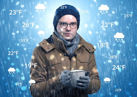 Boy freezing in warm clothing with weather condition concept Banco de Imagens