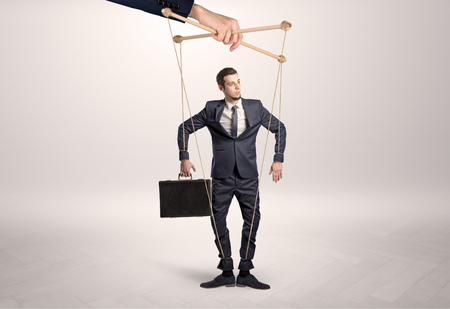 Puppet businessman leaded by a huge hand Archivio Fotografico
