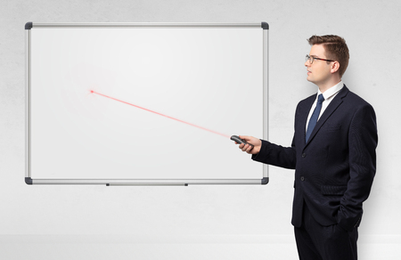 Businessman with laser pointer and copyspace white blackboard