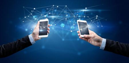 Smartphones sharing business data Фото со стока