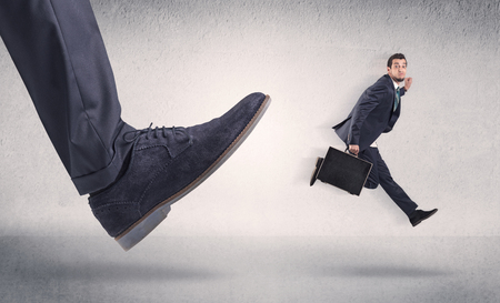 Small businessman kicked by big shoe Banco de Imagens