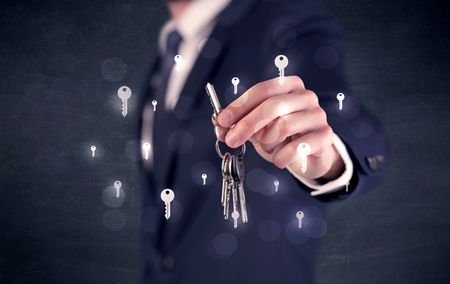 Businessman holding keys with keys around Stock fotó - 115943133