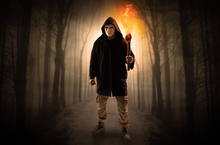 Man coming from dark forest with burning flambeau in his hand concept Stock Photo