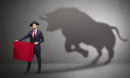 Businessman with bull shadow and toreador concept Standard-Bild