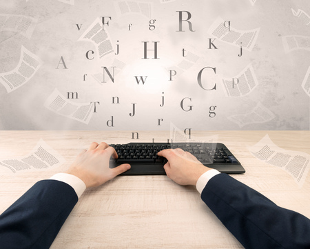 Elegant businessman hand typing with fluttering papers around Stock Photo