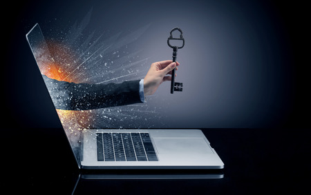 Hand with vintage huge key coming out of a laptop
