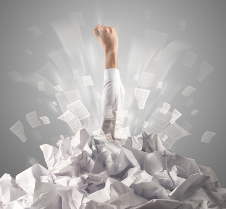 Hand coming out from paper pile Stock Photo - 116320622