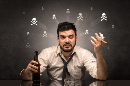 Drunk man sitting at table with skulls concept