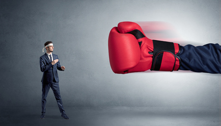 Little man fighting with big red boxing glove 写真素材