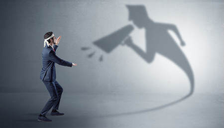 Businessman fighting with his bossy shadow Фото со стока