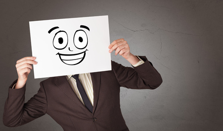 Student holding a paper with laughing emoticon in front of his face