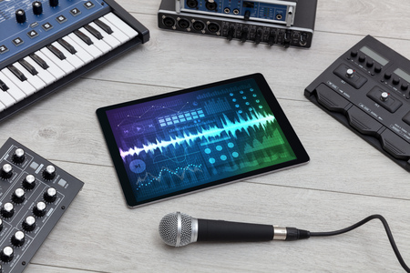 Music instruments and tablet with recording app Фото со стока