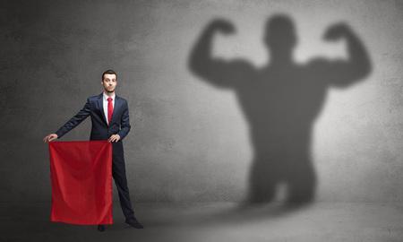 Businessman with strong hero shadow and toreador concept Standard-Bild
