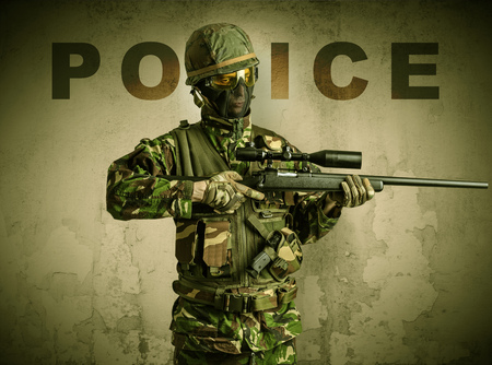 Armed soldier with damaged wall background