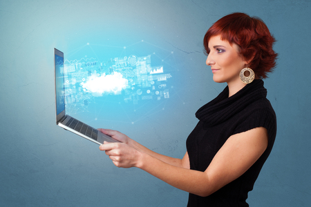 Woman holding laptop with cloud based system notifications
