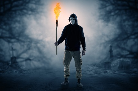 Man coming out from a thicket with burning flambeau Stock Photo