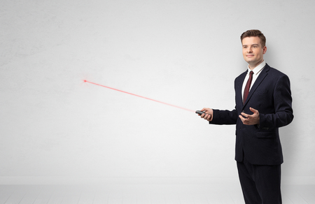 Businessman with laser pointer and copyspace white wall Stockfoto