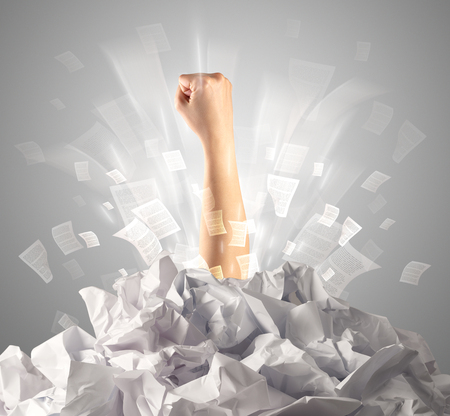 Hand coming out from paper pile Stock Photo - 117364543