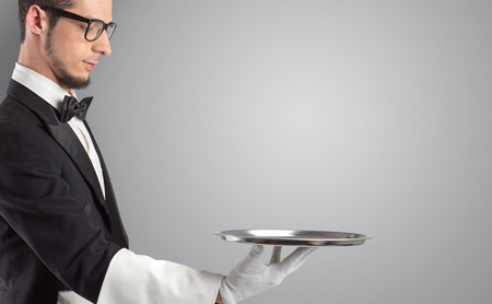 Waiter serving with white gloves and steel tray Фото со стока