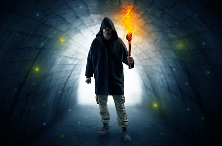 Man walking with burning flambeau in a dark tunnel
