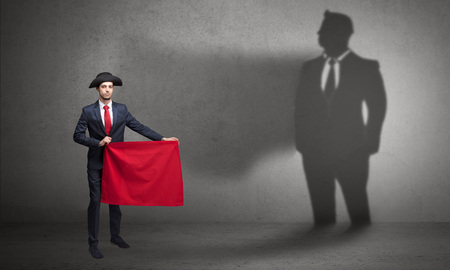 Businessman with toreador concept and his shadow on the background Reklamní fotografie