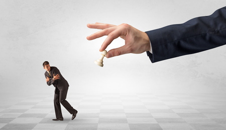 Small businessman running away from big hand with chessman concept Banco de Imagens - 118482050