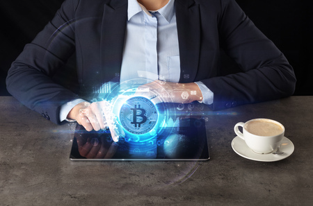 Business woman working on tablet with cryptocurrency concept