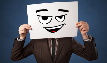 Person holding a paper in front of his face with doodle emoticon