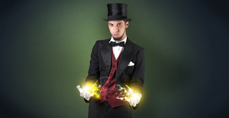Magician holding his sparkling power between his two hand Standard-Bild - 119155966
