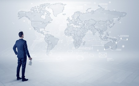 Businessman standing with his back and looking at a worldwide map with objects in his hand