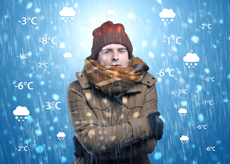 Young man freezing in warm clothing with weather condition and forecast concept Stock Photo