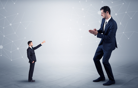 Small businessman aiming at a big businessman with connection and network concept Stock fotó