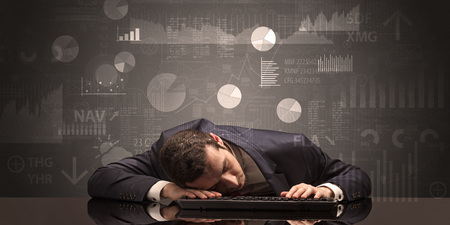 Young businessman sleeping with charts, graphs and reports on the background Foto de archivo
