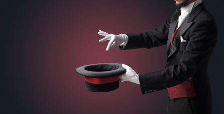 Illusionist white hand wants to conjure with magic wand from a black cylinder something Standard-Bild - 119157543