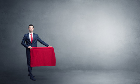 Businessman standing with red toreador cloth in his hand in an empty room Imagens