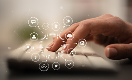 Business woman hand typing on keyboard with application icons around Stok Fotoğraf