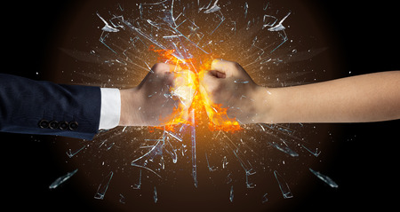 Two hands fighting and breaking a glass into small pieces Stock Photo