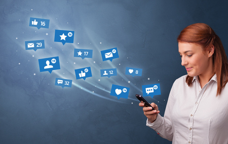 Young person using phone with flying social media icons around Stock Photo