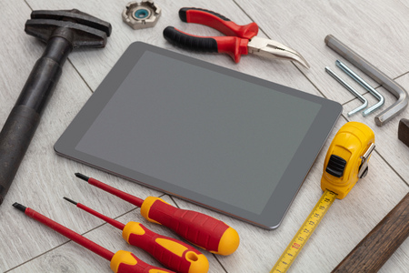 Tablet with empty screen and construction tools around